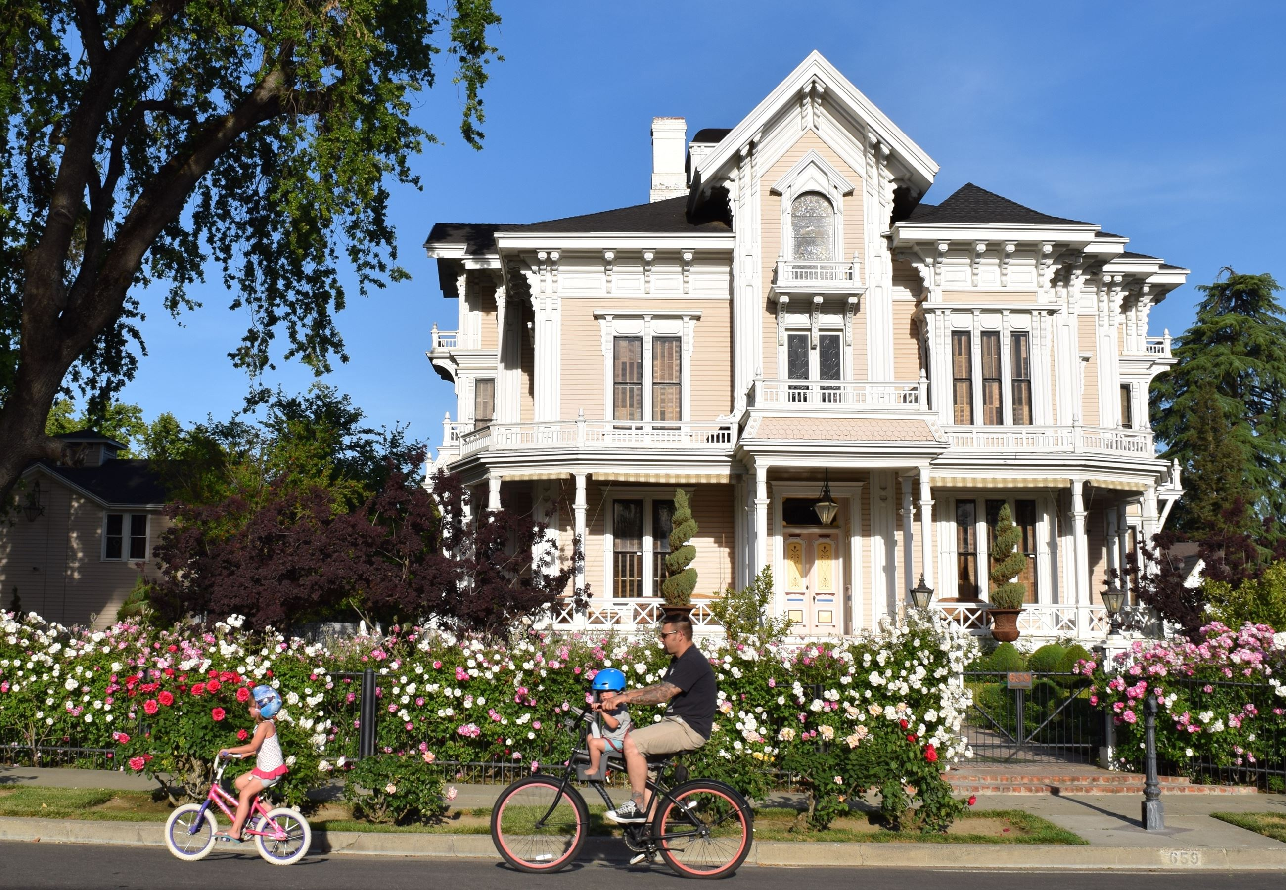 Family Biking in Front of Gable Mansion