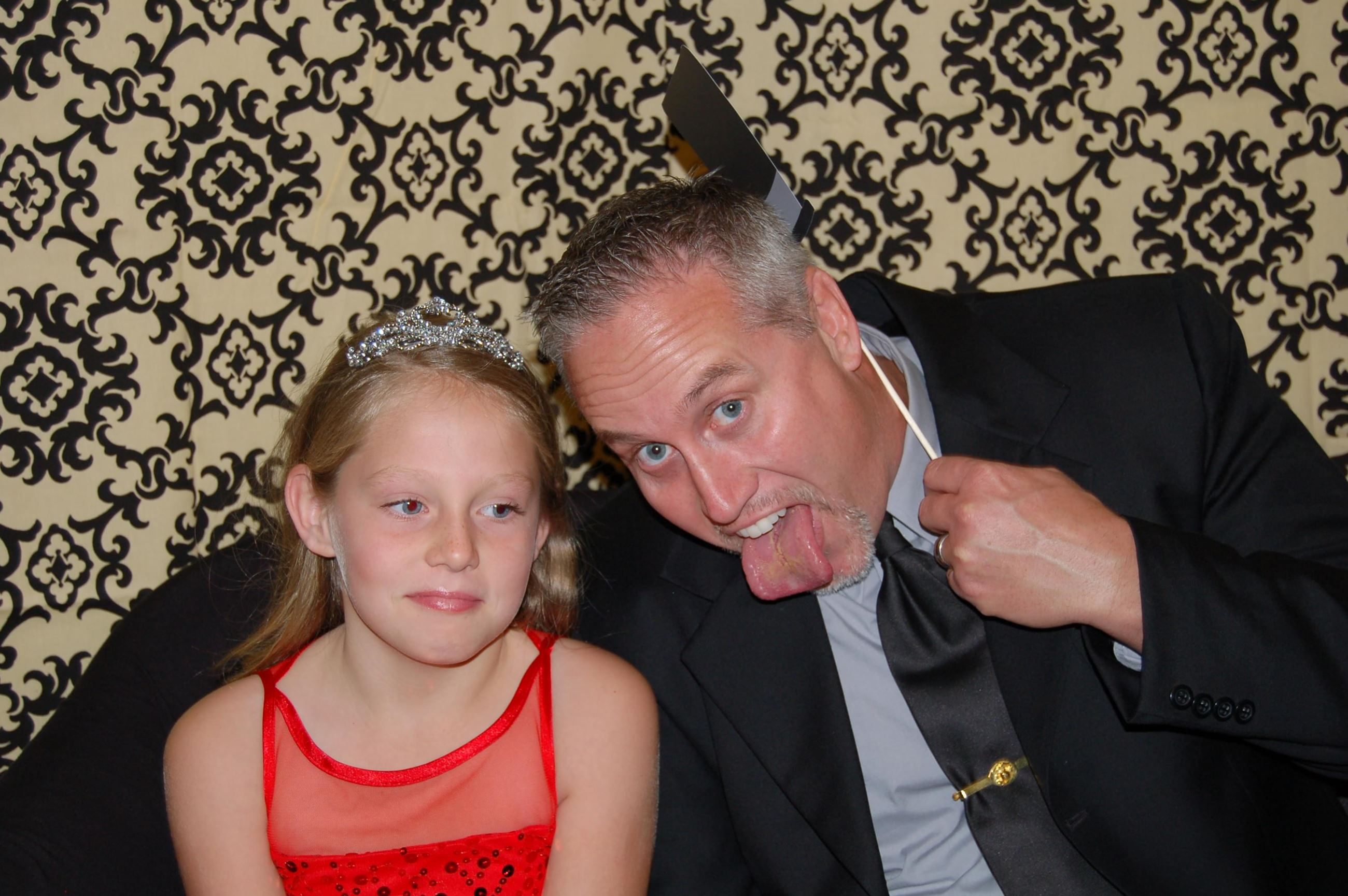Dad making a goofy face and girl smiling at Father Daughter Dinner Dance
