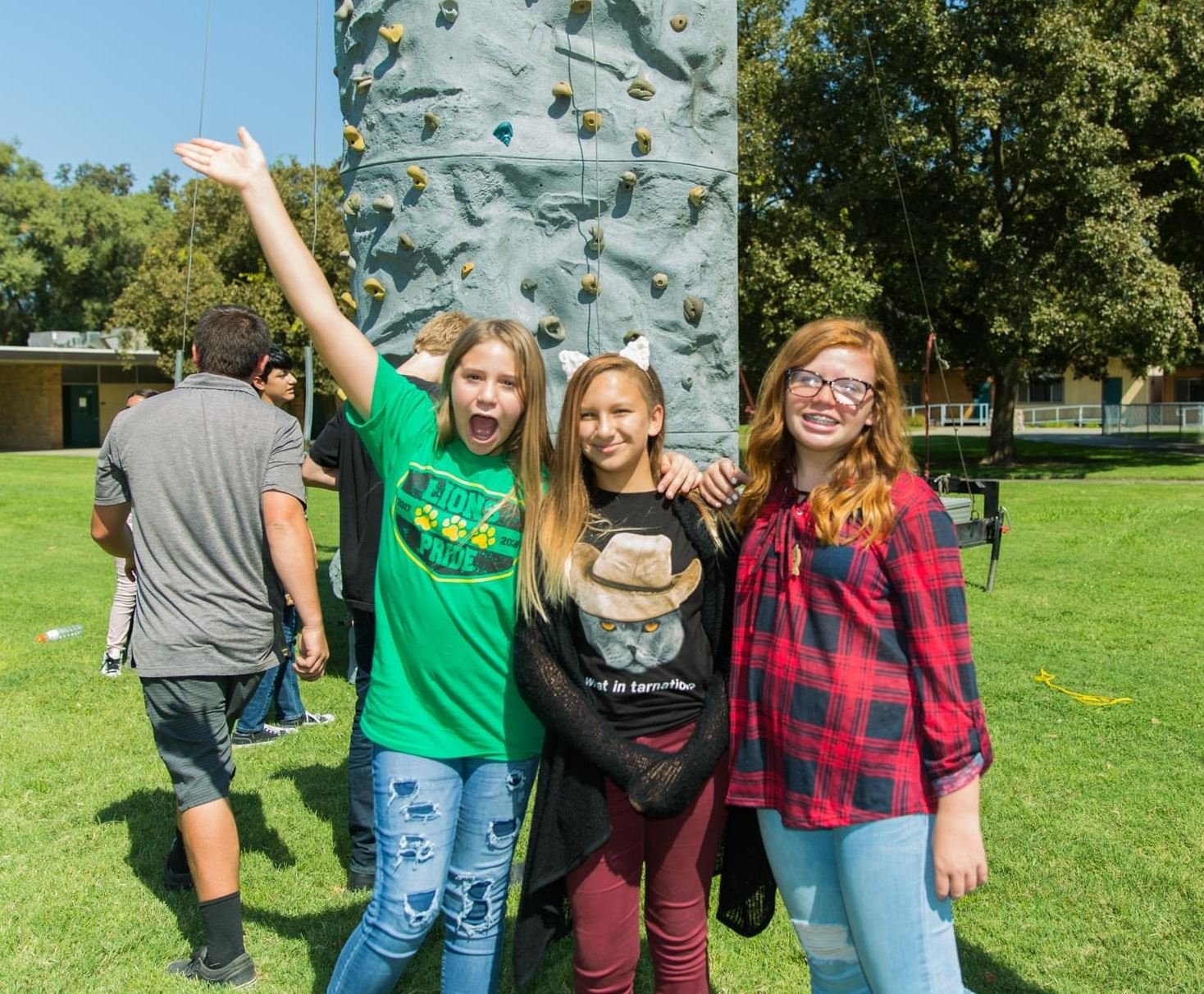Three girls by rock climbing wall